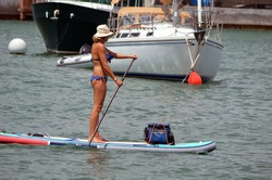 Tall slender woman paddling a paddle board in a blue bikini.
