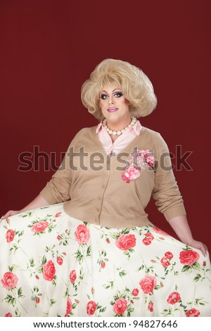 Tall, smiling drag queen with floral outfit
