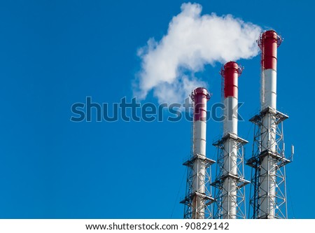 Tall smokestacks convey smoke into the air. Global warming and climate changing.