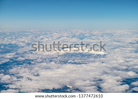 Tall Snowed Peak Mountains peaking through the white clouds with sunny day #1377472610