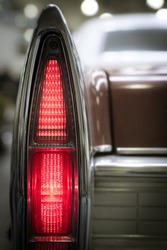 Tall thin pointed rear vintage tail light in the wing of an oldtimer classic motor car illuminated to show the red coloring, close up view.