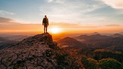 Tall tourist guide on rock. Hiker with sporty backpack stand on cliff above misty valley at sunset. Mountain meadow in spring or autumn. Vivid and strong vignetting effect. Horizontal, copy space