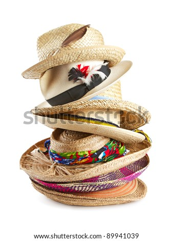 Tall vertical stack of straw brimmed hats in a variety of shapes, textures, colors, and sizes, trimmed with ribbons, feathers, and raffia. Isolated on white background, vertical format.