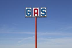 Tall vintage gas sign bight desert light.
