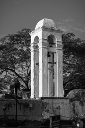 Tall white Bell tower at the maritime museum in Galle fort black and white photograph, evening bright light hits the side of the tower.