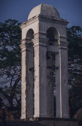 Tall white Bell tower at the maritime museum in Galle fort photograph, evening bright light hits the side of the tower.