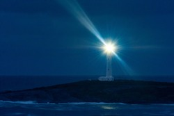 Tall white lighthouse at night with rays of light radiating out