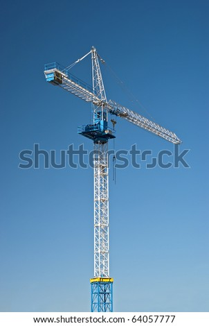 Tall white tower crane against bright blue sky.