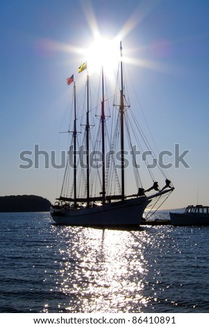 Tall wind sailing schooner at dock back lit by rising sun