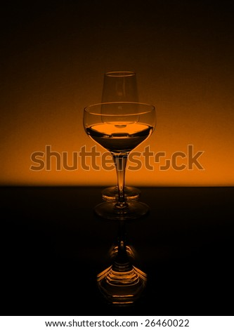 Tall wineglasses in black and orange against an orange background