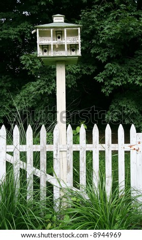 tall wooden birdhouse in garden setting
