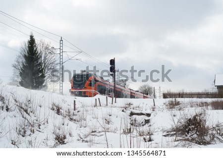 Tallinn, Estonia, March, 15, 2019: Diagonal view on high speed train runs on rail way tracks and trees in the background. Estonian railways electric high speed passenger commuter train.  #1345564871