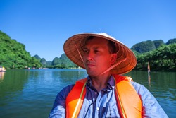 Tam Coc National Park, guide ride on the river in long boats, a tour of the river caves; A man in a traditional Vietnamese hat floats in a boat