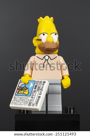 Tambov, Russian Federation - February 07, 2015 Lego Abraham Jay-Jedediah Abe Simpson minifigure with newspaper on black background. Studio shot.