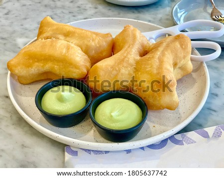 Tammy. two pieces Chinese breadsticks with Thai Pandan Custard on a white ceramic plate for breakfast Zdjęcia stock ©
