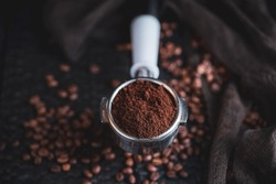 Tamped puck of coffee grounds within basket of portafilter and coffee beans spilled around in a dark and moody scene of natural light.