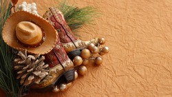 tan and brown cowboy boots and hat laying with pine cones, rustic berries on a brown textured background with writing space