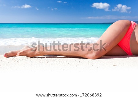 Tan slim legs lying on white sandy beach near sea, no face