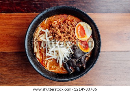 Tan Tan Ramen: Japanese noodle in Tan Tan soup with mince pork, boiled egg, wood ear and sprout in black bowl. #1214983786
