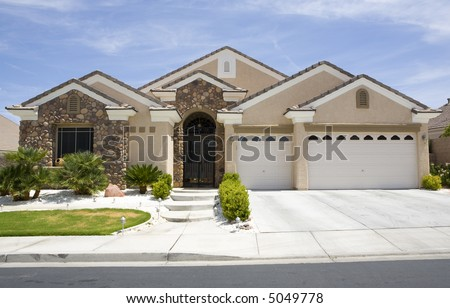 Tan two story stucco modern home with three car garage in Las Vegas Nevada