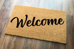 Tan Welcome Mat On Wood Floor Background..