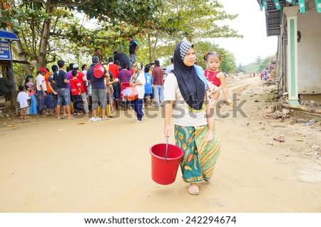 TANAH MERAH, KELANTAN - JANUARY 2: Flood victims receive food aid from NGO\'s in Kusial Baru village, Tanah Merah, Kelantan on January 2, 2015