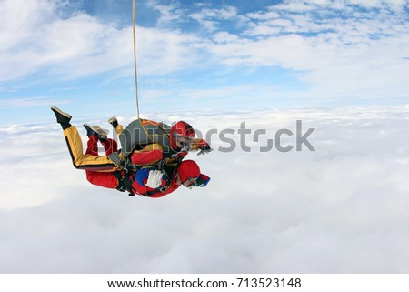 Tandem jump above white clouds. Side view.