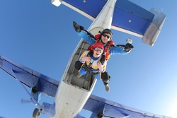 Tandem master and tandem passenger are jumping out of a plane.