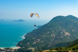 Tandem paragliders having fun paragliding over Dragon's Back hiking trail in Hong Kong, Asia