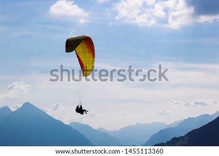 Tandem paragliding in Swiss Alps. Silhouettes of paragliders and beautiful mountains. Extreme sport, adventure sports. Adventurous lifestyle. Concept, conceptual