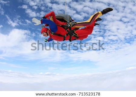 Tandem skydiving above clouds. Side view.