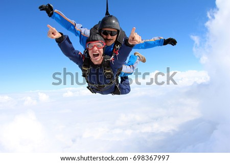 Tandem skydiving above the white clouds.