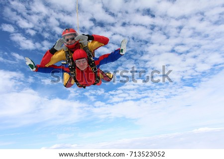 Tandem skydiving. Passenger and instructor are flying in the amazing sky.