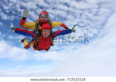 Tandem skydiving. Passenger is smiling, instructor is going to open a parachute.