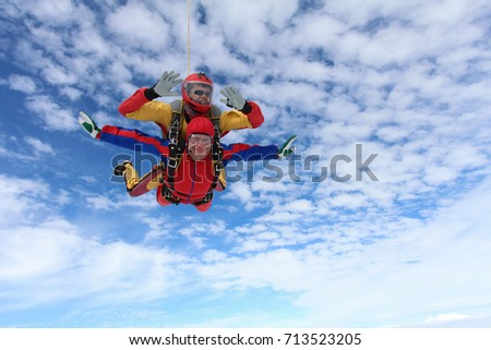 Tandem skydiving. Passenger is smiling, instructor is looking to altimeter.