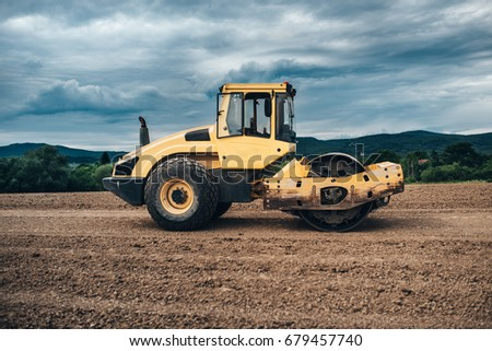 Tandem vibration roller compactor working on highway ground construction site