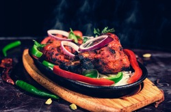 Tandoori chicken is chicken dish prepared by roasting chicken marinated in yoghurt and spices in a tandoor, a cylindrical clay oven. It is a popular dish from the Indian.