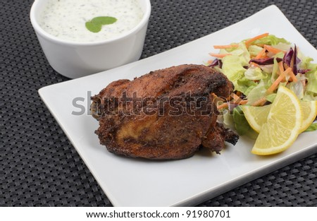 Tandoori chicken served with salad, mint raita and lemon slices