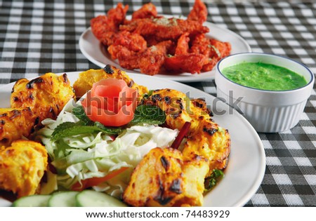 tandoori chicken tikka with salad and sauce