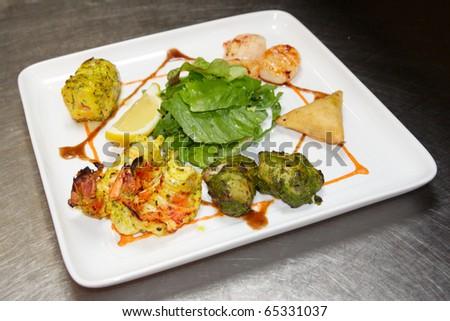 Tandoori indian style food on restaurant kitchen table - stock photo