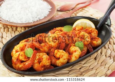 Tandoori prawns on a cast iron sizzle platter, served with basmati rice.