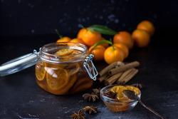 tangarine marmalade jam in glass jar. dark food photo style. Christmas winter or autumn mood. Homemade citrus cinnamon and anise stars marmalade