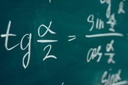 Tangent alpha sine cosine. Trigonometric formula written on the board.