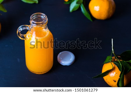 Tangerine juice concentrate in bottle with fruits on charcoal wooden table Stock fotó ©