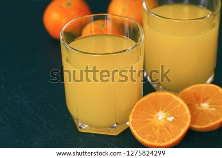 tangerine juice in the cups and the halves of the tangerines closeup. fresh tangerine juice. #1275824299