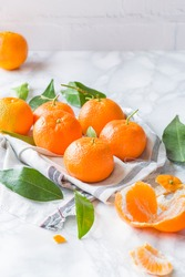 Tangerine, mandarine or clementine  with green leaf and slices isolated on white marble background.