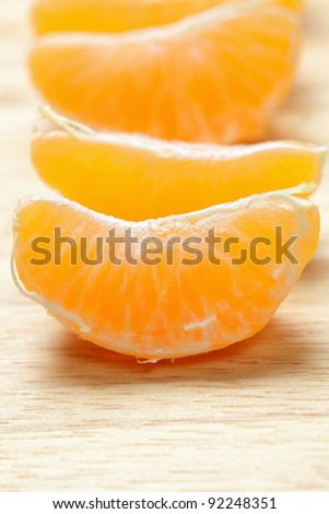 Tangerine slices in a row on wooden board