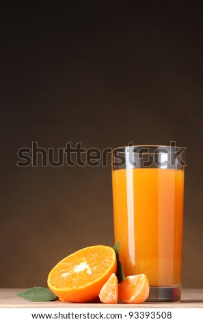 Tangerines and juice glass on wooden table on brown background