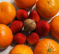 Tangerines and strawberries in symmetry and in the center a walnut. Decorative photo