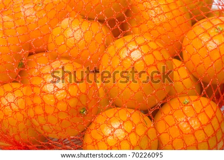 tangerines in red plastic net. fruit background